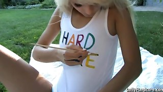 Lolly paints her body outdoors